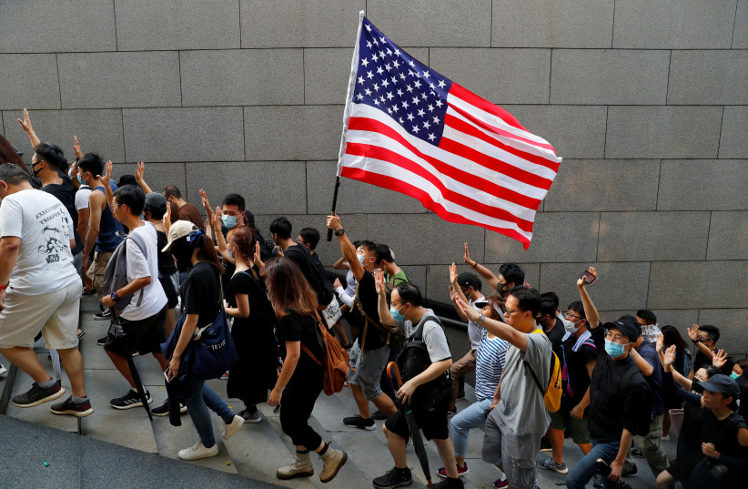 Protesters hold up five fingers and a U.S. flag during a rally to the U.S. Consulate General in Hong Kong, China September 8, 2019. (photo credit: REUTERS/ANUSHREE FADNAVIS)
