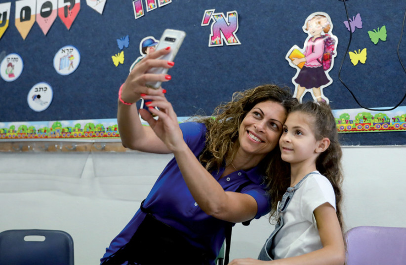 A mother takes a selfie with her first-grade daughter on the first day of school (photo credit: MARC ISRAEL SELLEM)