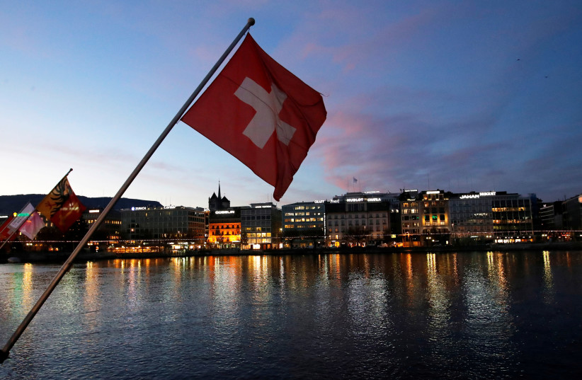 A Swiss flag is pictured during the sunrise on the Commercial and Financial District in Geneva, Switzerland, November 23, 2017 (photo credit: REUTERS/DENIS BALIBOUSE)