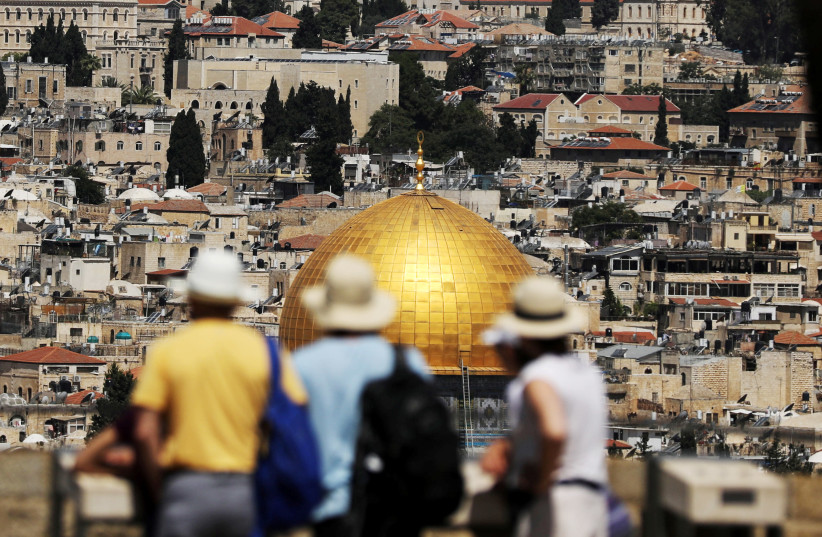 Tourists look at the Dome of the Rock, located in Jerusalem's Old City on the compound known to Muslims as Noble Sanctuary and to Jews as Temple Mount, June 21, 2018 (photo credit: REUTERS/AMMAR AWAD)