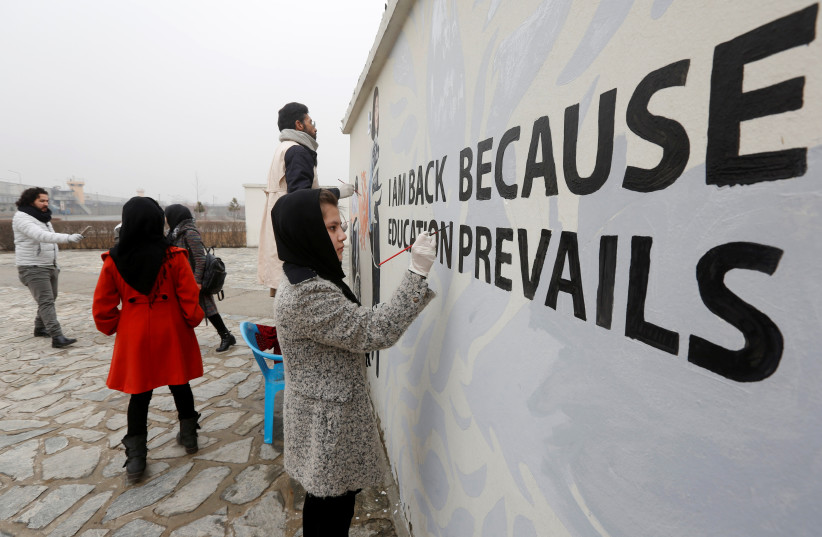 Afghan Artlords paint a message on a wall at the American University of Afghanistan in Kabul (photo credit: REUTERS)