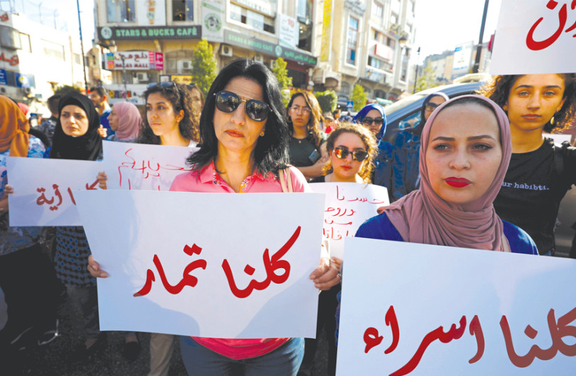 A DEMONSTRATOR holds a banner demanding legal protection for women, in Ramallah on September 4. (photo credit: MOHAMAD TOROKMAN/REUTERS)