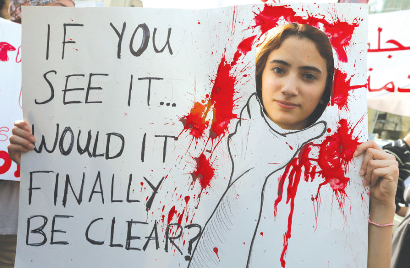 AN ACTIVIST holds a banner during a march protesting domestic violence against women, in Beirut on March 8, 2014, International Women's Day. (photo credit: JAMAL SAIDI/ REUTERS)