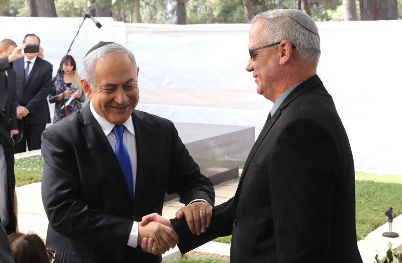 Prime Minister Benjamin Netanyahu shaking hands with Blue and White leader Benny Gantz at a memorial service honoring Shimon Peres (photo credit: MARC ISRAEL SELLEM)