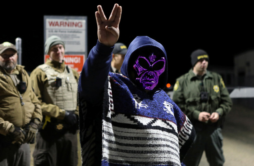 An attendee wears an alien mask at the gate of Area 51 as an influx of tourists are expected, responding to a call to 'storm' the secretive U.S. military base, believed by UFO enthusiasts to hold government secrets about extra-terrestrials, in Rachel, Nevada, September 20, 2019 (photo credit: JIM URQUHART/REUTERS)