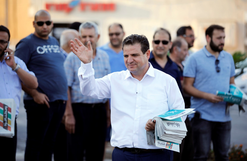 Ayman Odeh, leader of the Joint List, gestures as he hands out pamphlets during an election campaign event in Tira last week.  (photo credit: REUTERS/AMIR COHEN)