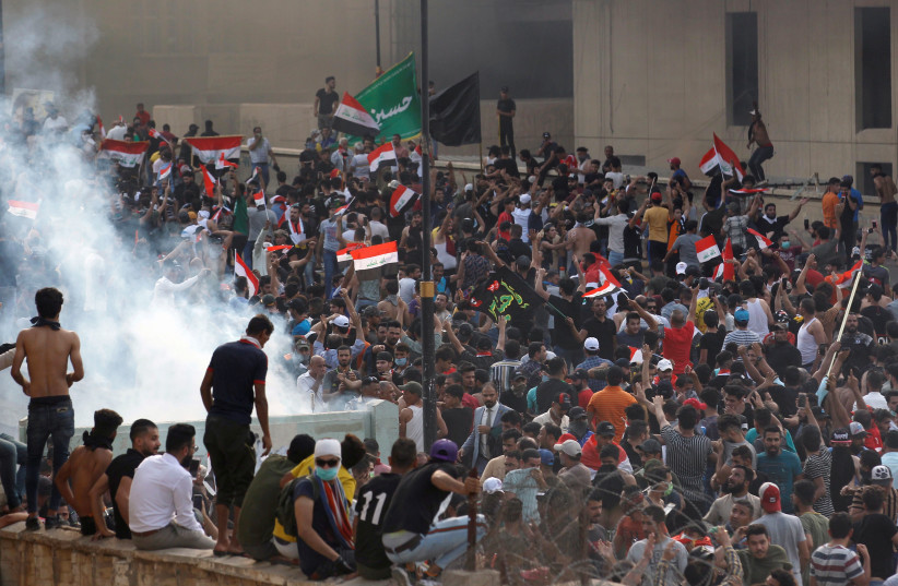 Demonstrators disperse as Iraqi Security forces use tear gas during a protest against government corruption amid dissatisfaction at lack of jobs and services at Tahrir square in Baghdad, Iraq October 1, 2019 (photo credit: REUTERS/THAIER AL-SUDANI)
