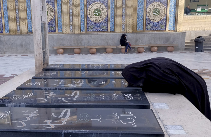 Iranian woman kisses the grave of a person, who was killed during the Iran-Iraq war (1980-88), at a holy shrine in northern Tehran (photo credit: REUTERS)