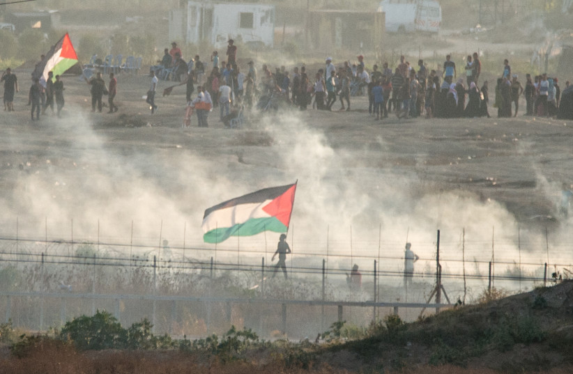Palestinians riot in front of the Bureij refugee camp, in the central Gaza Strip. IDF troops use tear gas in an attempt to deter them from getting close to the fence. Gaza envelope, Aug 2, 2019 (photo credit: KOBI RICHTER/TPS)