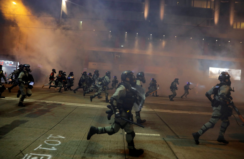 Riot police chase away anti-government protesters near Causeway Bay metro station, after leader Carrie Lam announced emergency laws that would include banning face masks at protests, in Hong Kong, China October 4, 2019 (photo credit: REUTERS/SUSANA VERA)