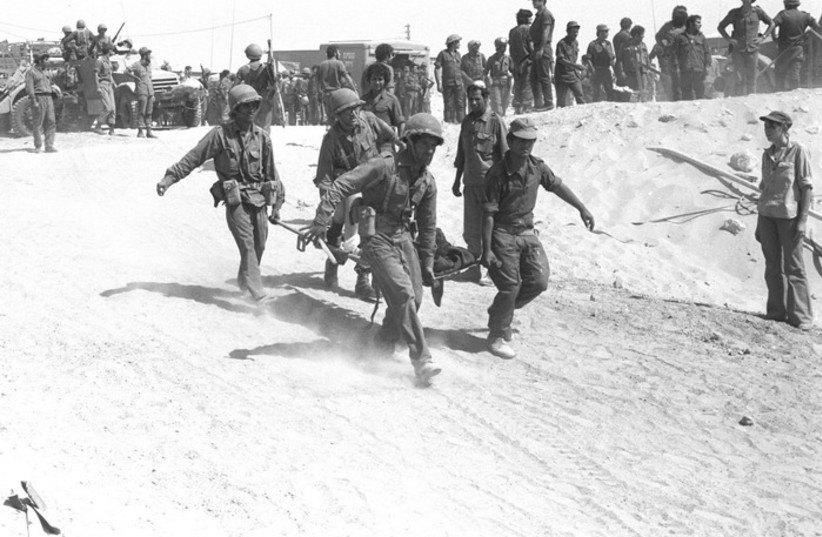 IDF medical crew evacuating an injured soldier from the battle field during Yom Kippur War (photo credit: IDF FLICKR)
