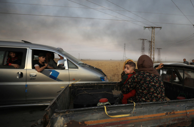 A woman with a baby sits at a back of a truck as they flee Ras al Ain town (photo credit: REUTERS/RODI SAID)