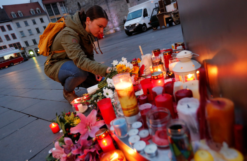 People place candles at central market square in Halle, Germany October 10, 2019, after two people were killed in a shooting (photo credit: REUTERS/FABRIZIO BENSCH)