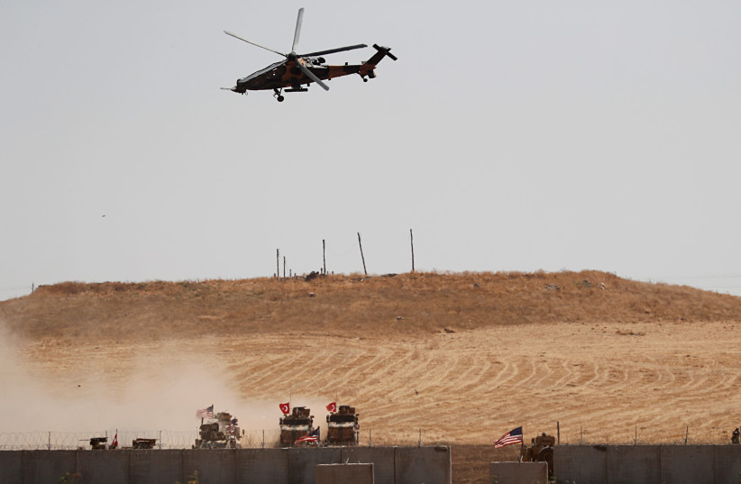 A Turkish military helicopter flies over as Turkish and U.S. troops return from a joint U.S.-Turkey patrol in northern Syria, as it is pictured from near the Turkish town of Akcakale, Turkey, September 8, 2019 (photo credit: REUTERS/MURAD SEZER)