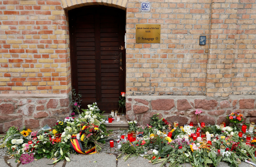 Flowers and candles are seen outside the synagogue in Halle, Germany October 10, 2019, after two people were killed in a shooting (photo credit: REUTERS/FABRIZIO BENSCH)