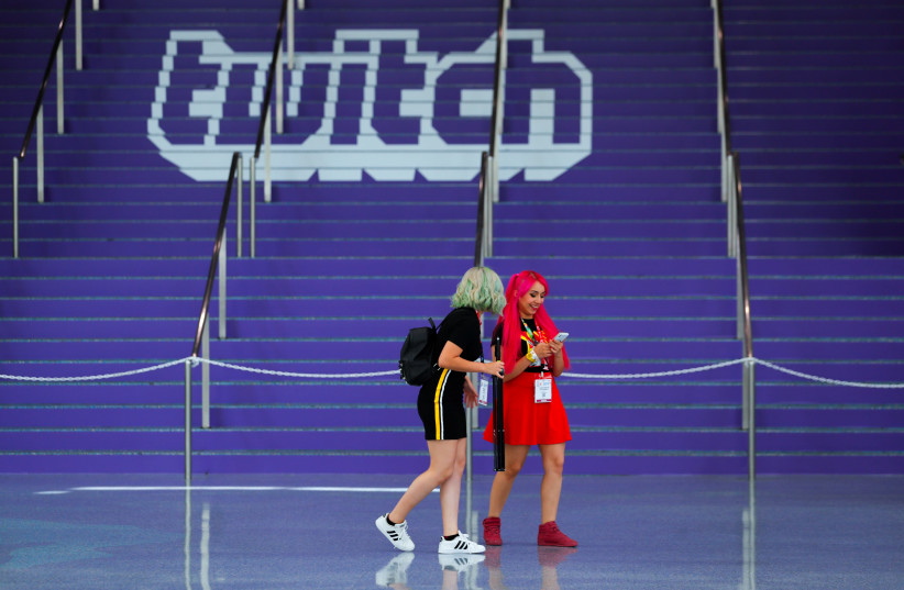 Attendees walk past a Twitch logo in Los Angeles (photo credit: REUTERS/MIKE BLAKE)
