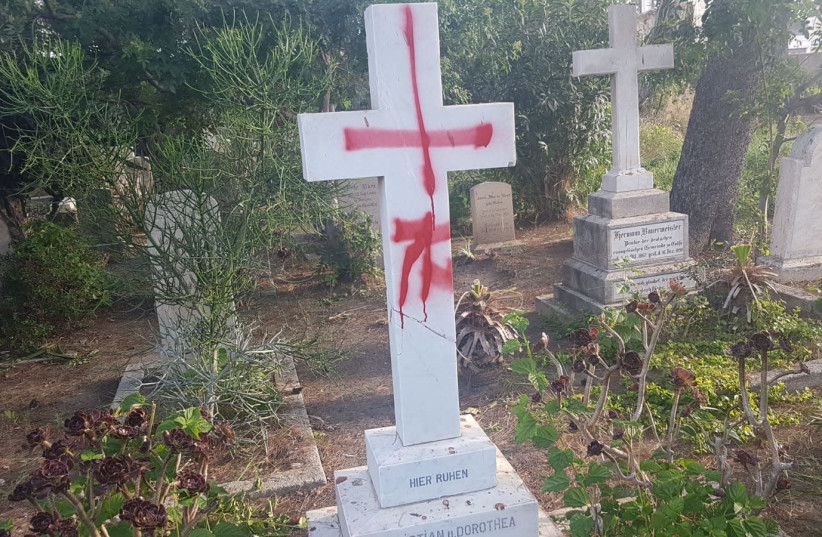 Tombstones desecrated with graffiti at the British cemetery in Haifa (photo credit: POLICE SPOKESPERSON'S UNIT)