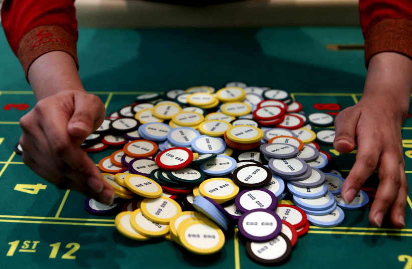 A casino dealer collects chips at a roulette table in Pasay city, Metro Manila (photo credit: ERIK DE CASTRO/ REUTERS)