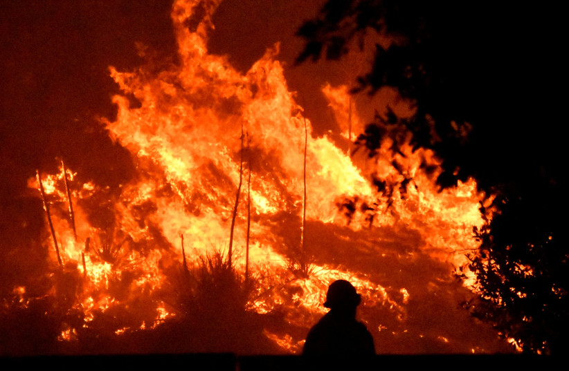 Firefighters battle a wind-driven wildfire called the Saddle Ridge fire in the early morning hours Friday in Porter Ranch, California, U.S., October 11, 2019. (photo credit: GENE BLEVINS / REUTERS)