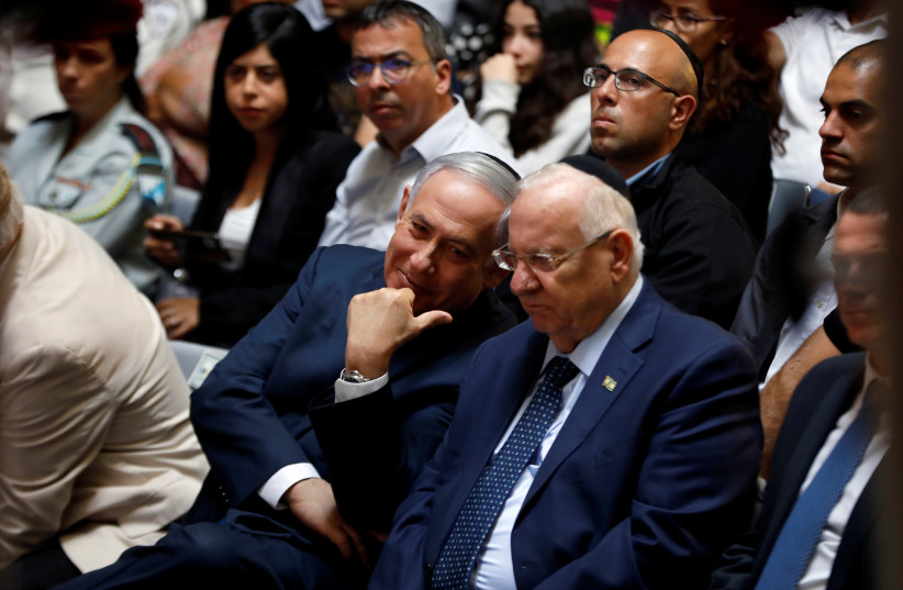 Israeli Prime Minister Benjamin Netanyahu chats with Israeli President Reuven Rivlin during a memorial ceremony for Israeli soldiers killed in the 1973 Middle East War at Mount Herzl Military Cemetery in Jerusalem October 10, 2019 (photo credit: REUTERS/Ronen Zvulun)