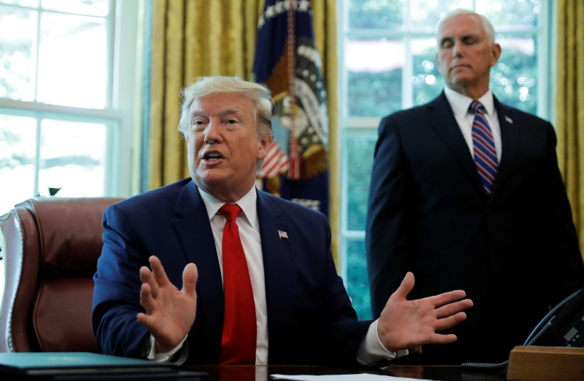 U.S. President Donald Trump talks about the United States imposing fresh sanctions on Iran as Vice President Mike Pence looks on in the Oval Office of the White House in Washington, U.S., June 24, 2019 (photo credit: REUTERS/CARLOS BARRIA)