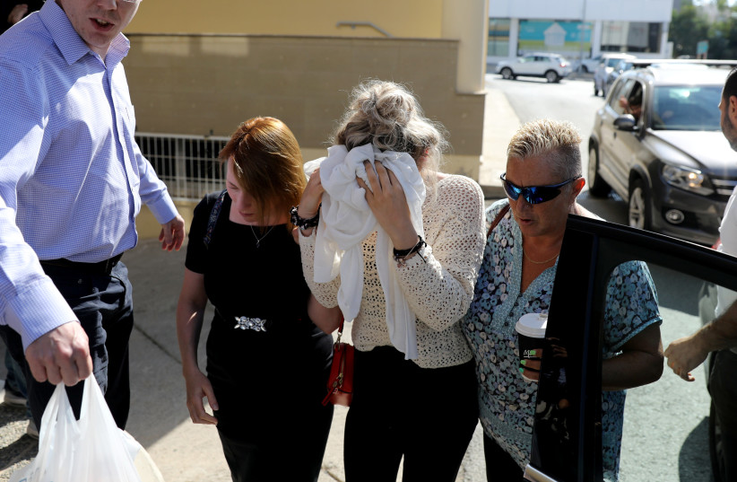 A 19-year-old British woman covers her face as she arrives at the Famagusta courthouse in Paralimni, Cyprus (photo credit: REUTERS/YIANNIS KOURTOGLOU)