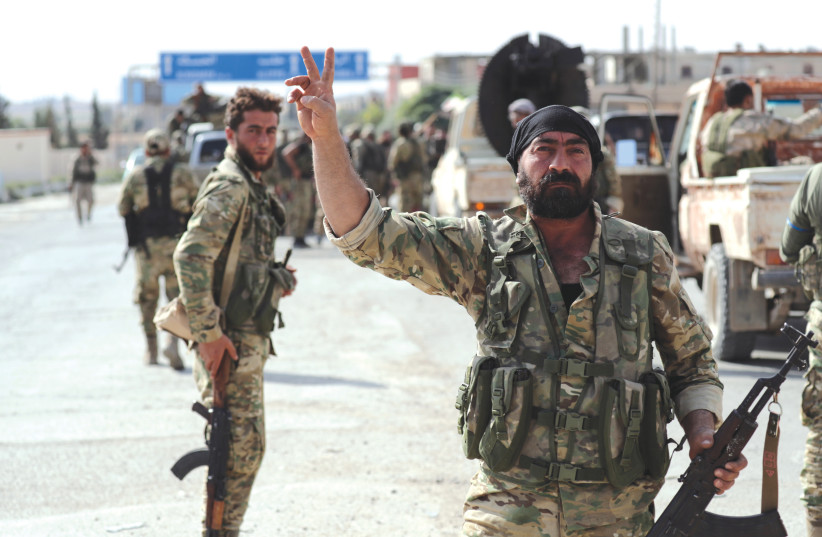 TURKEY-BACKED Syrian rebel fighter gestures to the camera at the border town of Tel Abyad, Syria, Monday.  (photo credit: KHALIL ASHAWI / REUTERS)
