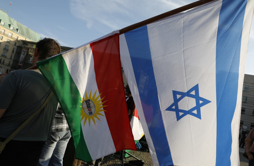 Protesters hold Kurdish and Israeli flags during a rally against the Turkish military operation in Syria, in Berlin, Germany, October 14, 2019 (photo credit: MICHELE TANTUSSI/REUTERS)