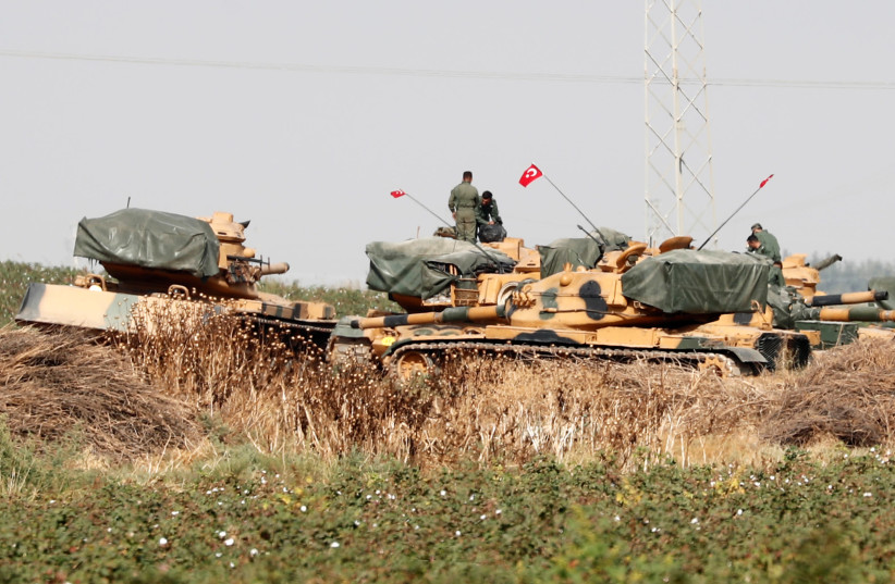 Turkish soldiers stand on top of tanks near the Turkish-Syrian border in Sanliurfa province, Turkey, October 15, 2019 (photo credit: REUTERS/MURAD SEZER)