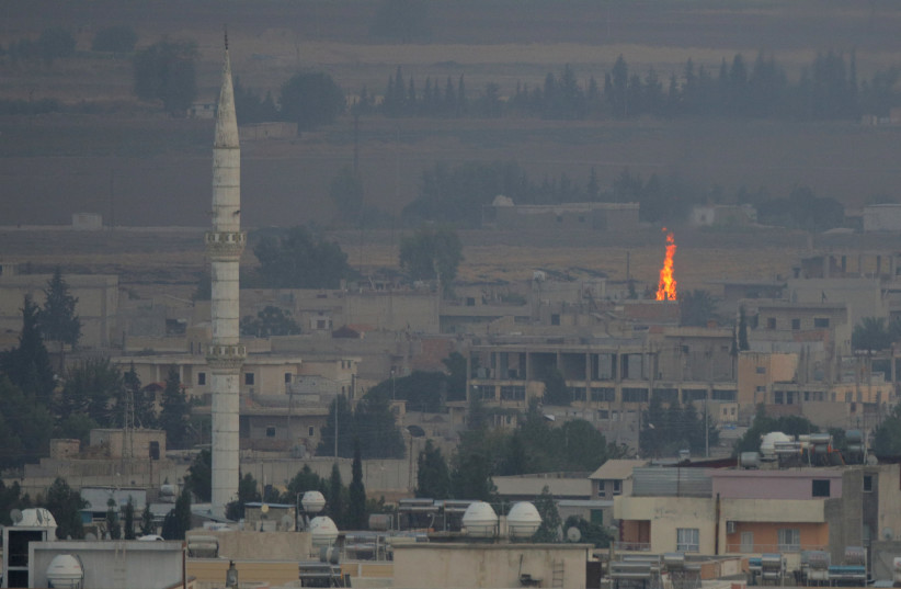 A fire is seen in the Syrian town of Ras al-Ain as seen from the Turkish border town of Ceylanpinar, Sanliurfa province, Turkey, October 17, 2019 (photo credit: REUTERS/STOYAN NENOV)