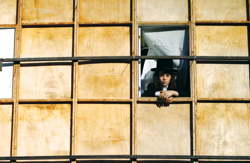 A BOY looks out through a window of a sukkah in Ashdod (photo credit: AMIR COHEN/REUTERS)