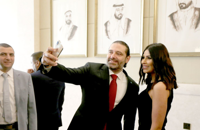 LEBANESE PRIME MINISTER SAAD HARIRI takes a selfie with a participant at the UAE-Lebanon Investment Forum in Abu Dhabi, UAE, on October 7.  (photo credit: SATISH KUMAR/REUTERS)
