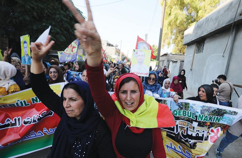 KURDISH AND ARAB protesters chant slogans against Turkish President Tayip Erdogan in Qamishli, Syria, Wednesday. (photo credit: MOHAMMAD HAMED / REUTERS)