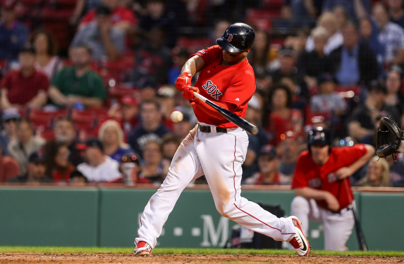 Boston Red Sox third baseman Rafael Devers (11) hits an RBI single during the ninth inning to defeat the Baltimore Orioles at Fenway Park. (photo credit: PAUL RUTHERFORD / USA TODAY)