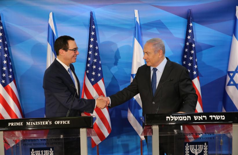 U.S. Treasury Secretary Steven Mnuchin shakes hands with Israeli Prime Minister Benjamin Netanyahu, who urged him to crank up pressure on Iran at a press conference in Jerusalem (photo credit: AMIT SHABI/YEDIOTH ACHRONOTH/POOL)