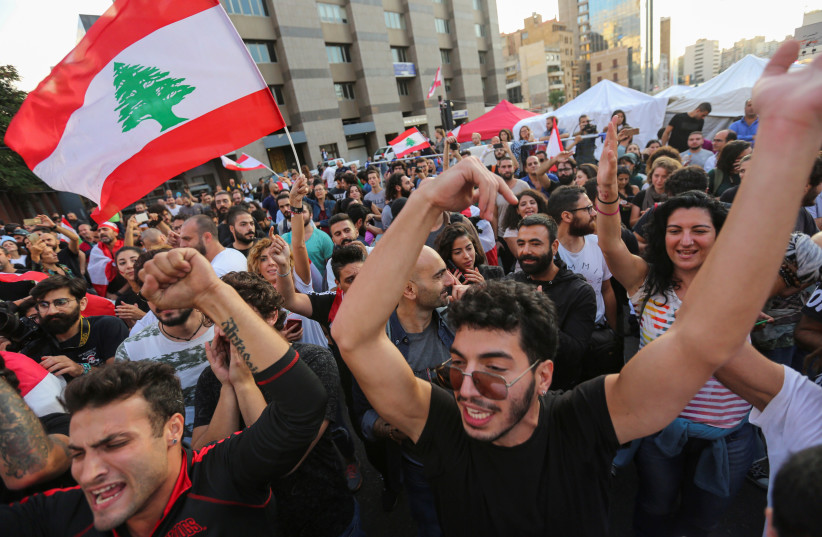 Protestors celebrate after Lebanon's Prime Minister Saad al-Hariri announced his resignation in Beirut, Lebanon October 29, 2019 (photo credit: AZIZ TAHER/REUTERS)