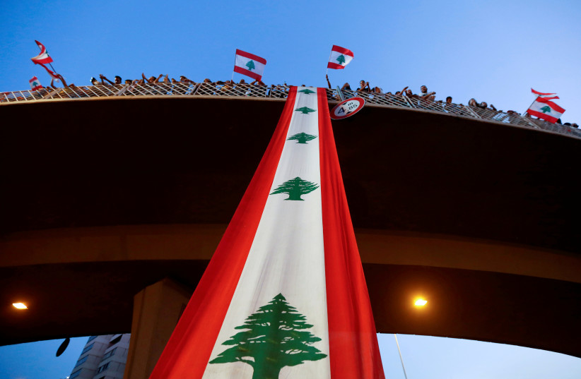 Demonstrators stand on a bridge decorated with a national flag during an anti-government protest along a highway in Jal el-Dib, Lebanon, October 21, 2019 (photo credit: MOHAMED AZAKIR / REUTERS)