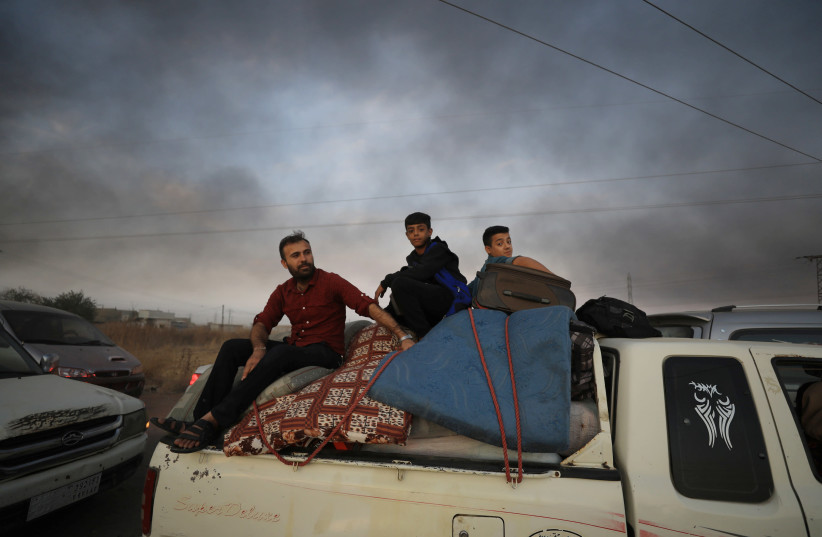 People sit on belongings at a back of a truck as they flee Ras al Ain in Syria. (photo credit: REUTERS)