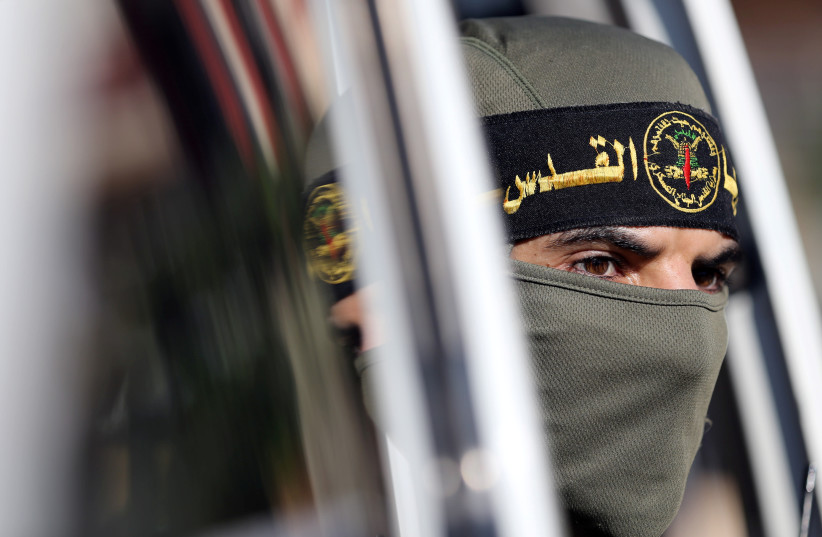 A Palestinian Islamic Jihad militant looks out of a vehicle during a military show marking the 32nd anniversary of the organisation's founding, in the central Gaza Strip October 3, 2019 (photo credit: REUTERS/IBRAHEEM ABU MUSTAFA)