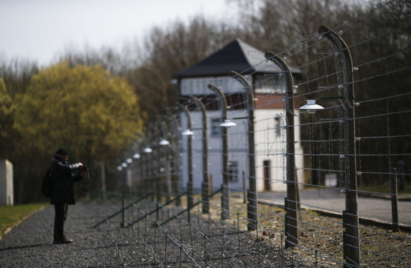 A visitor stands in front of a watchtower behind a fence on the grounds of the former Nazi concentration camp Buchenwald near Weimar (photo credit: REUTERS)