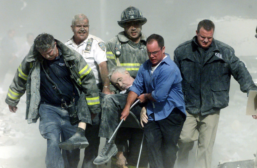 Rescue workers carry mortally injured New York City Fire Department chaplain, the Rev. Mychal Judge, from the wreckage of the World Trade Center in New York City in this file photo from early September 11, 2001. The Chaplain was crushed to death by falling debris while giving a man last rites in the (credit: REUTERS)