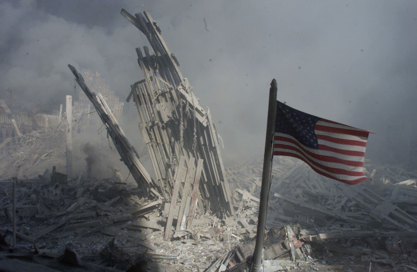 Am American flag flies near the base of the destroyed World Trade Center in New York, September 11, 2001. Planes crashed into each of the two towers, causing them to collapse (photo credit: REUTERS)