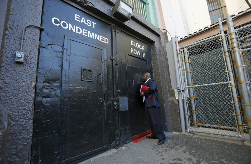 Lieutenant Sam Robinson, a public information officer at San Quentin State Prison, knocks on the door to the East Block for condemned prisoners during a media tour of California's Death Row in San Quentin, California (photo credit: REUTERS)