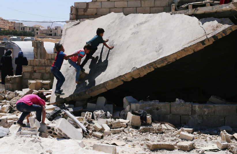 Syrian refugee kids play on a rubble of dismantled concrete huts at a makeshift Syrian refugee camp in the Lebanese border town of Arsal, Lebanon (photo credit: REUTERS/MOHAMED AZAKIR)