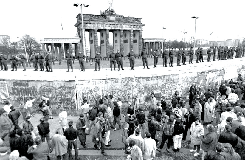 SOLDIERS STAND at ease on top of the Berlin Wall, in front of Brandenburg Gate, on November 10, 1989 (photo credit: ANDREW STAWICKI/TORONTO STAR/ZUMA PRESS/TNS)