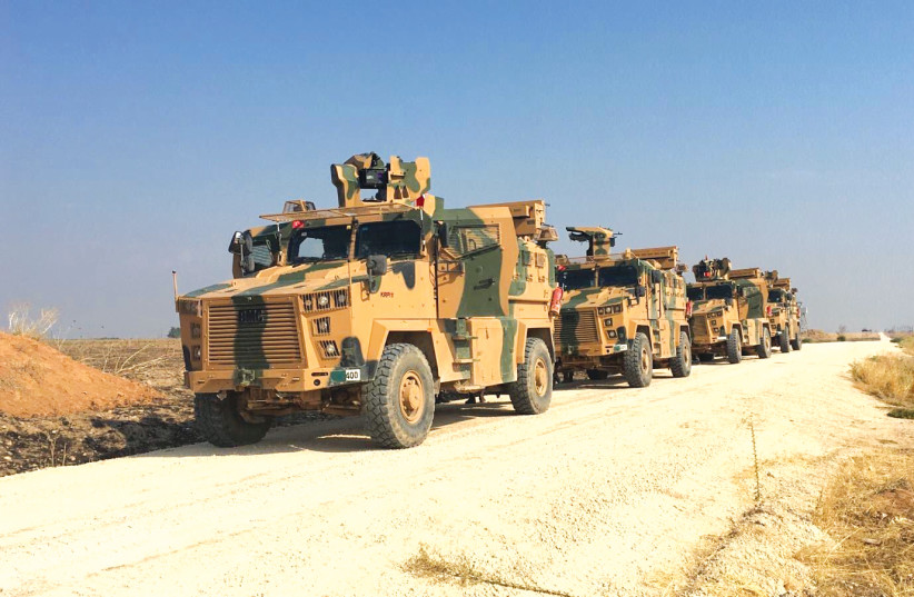 TURKISH MILITARY vehicles are seen on the Turkish-Syrian border before a joint Turkish-Russian patrol in northeast Syria, near the Turkish town of Kiziltepe. (photo credit: REUTERS)