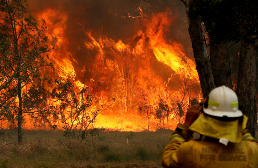 A firefighter on property protection watches the progress of bushfires in Old Bar, New South Wales, Australia November 9, 2019 (photo credit: AAP IMAGE/SHANE CHALKER/VIA REUTERS)