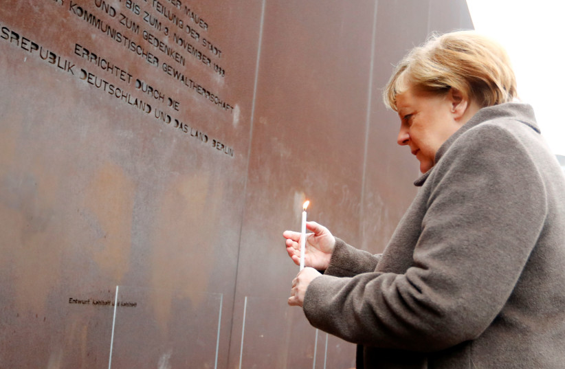 German Chancellor Angela Merkel lights a candle at the memorial of the divided city and the victims of communist tyranny during a ceremony marking the 30th anniversary of the fall of the Berlin Wall at the Wall memorial on Bernauer Strasse in Berlin, Germany, November 9, 2019 (photo credit: REUTERS/FABRIZIO BENSCH)