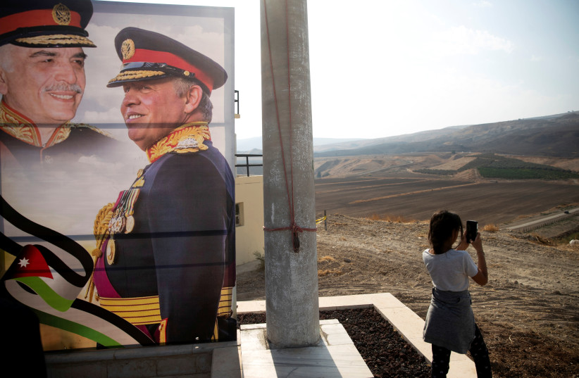 "A picture of Jordanian King Abdullah and his father, the late King Hussein, is seen as a girl visits the ""Island of Peace"" in an area known asNaharayim in Hebrew and Baquora in Arabic, on the Jordanian side of the border with Israel November 9, 2019 (photo credit: REUTERS)"