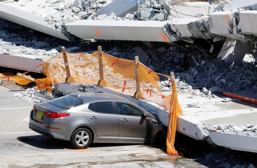 A damaged car is seen partially trapped as workers remove debris from a collapsed pedestrian bridge at Florida International University in Miami, Florida, U.S., March 16, 2018. (photo credit: REUTERS/JOE SKIPPER)